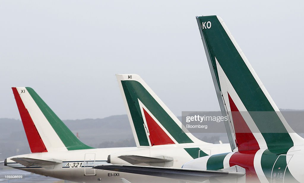 Logos sit on the tailfins of Alitalia SpA aircraft parked at Fiumicino airport in Rome, Italy, on Friday, Jan. 11, 2013. Former Italian Prime Minister Silvio Berlusconi's economic adviser said the European debt crisis has left his country's companies vulnerable to takeovers by foreign rivals and urged the government to prepare defences. Photographer: Alessia Pierdomenico/Bloomberg via Getty Images