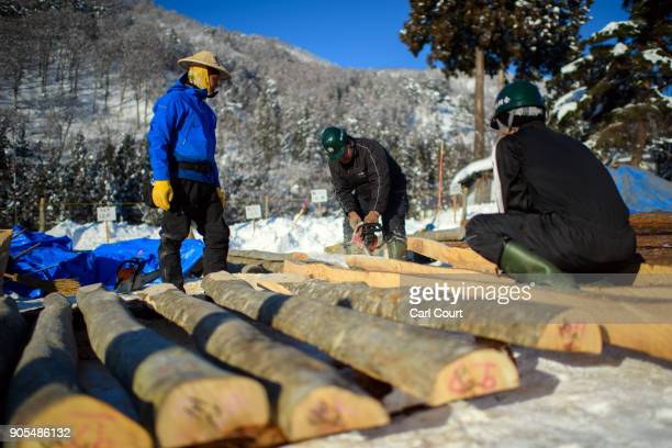 Logs are cut as villagers work on building a shrine during preparations for the Nozawaonsen Dosojin Fire Festival on January 14 2018 in Nozawaonsen...