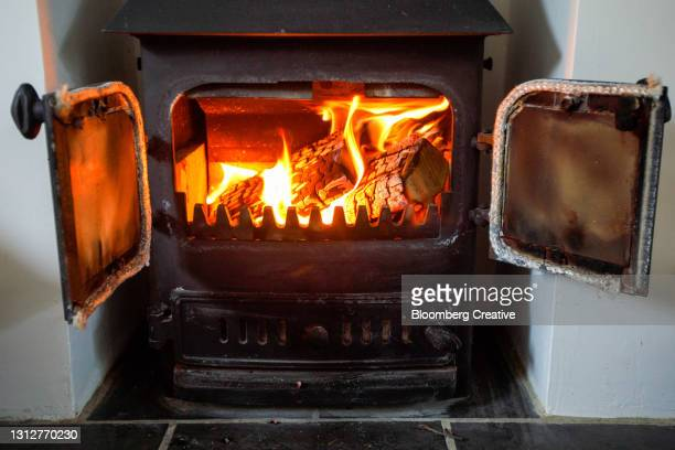 logs burning on a wood burner - wood material stock pictures, royalty-free photos & images