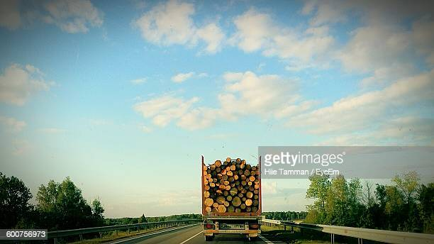 Logs In Truck On Street Against Sky