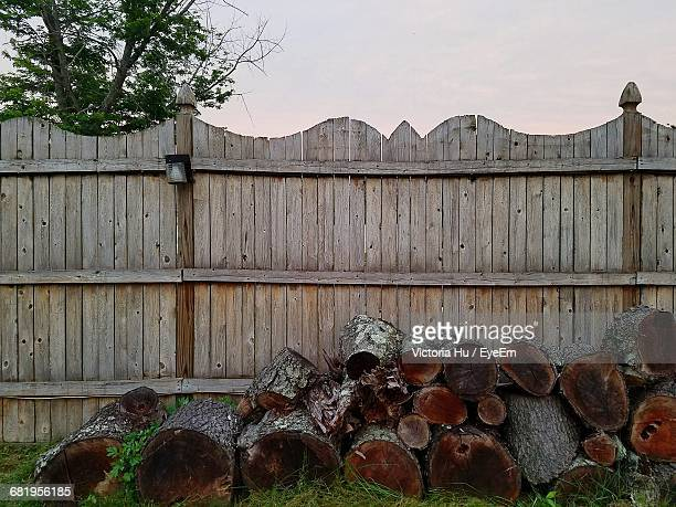 Logs In Yard By Fence Against Clear Sky During Sunset