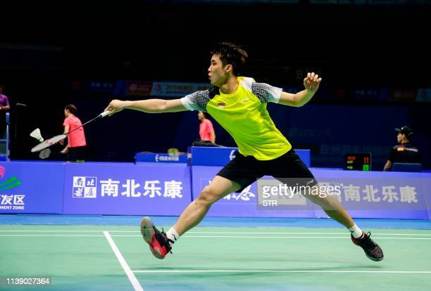 Loh Kean Yew of Singapore hits a return against Shi Yuqi of China during their men's singles first round match at the 2019 Badminton Asia...