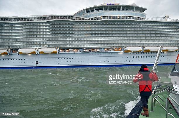 A Loire river pilot looks at the Harmony of the Seas cruise ship as it leaves the STX shipyard of SaintNazaire western France for a threeday offshore...