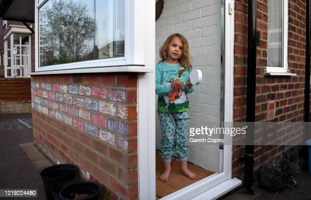 Lois Copley-Jones aged 5, daughter of the photographer claps on her doorstep as part of 'Clap for Carers' in support of the NHS on April 16, 2020 in...