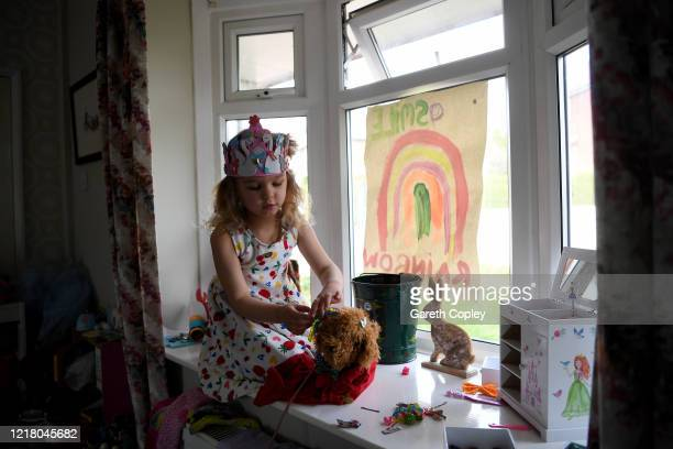 Lois Copley-Jones, aged 5, who is the photographer's daughter, plays with her toys in the living room window on April 10, 2020 in Newcastle Under...