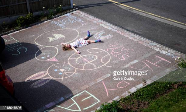 Lois CopleyJones aged 5 who is the photographer's daughter uses chalks to draw Easter celebration pictures on her driveway on April 10 2020 in...