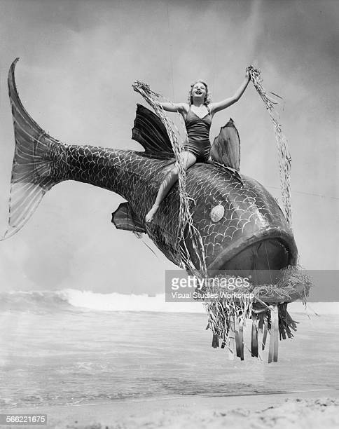 Lois Davis rides a giant plastic fish held up with invisible wires to advertise for the annual Mardi Gras festivities Venice California early to mid...