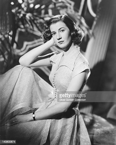Lois Maxwell , Canadian actress, wearing a white button-front dress, posing with her elbow resting on her knee and her head resting against her hand,...
