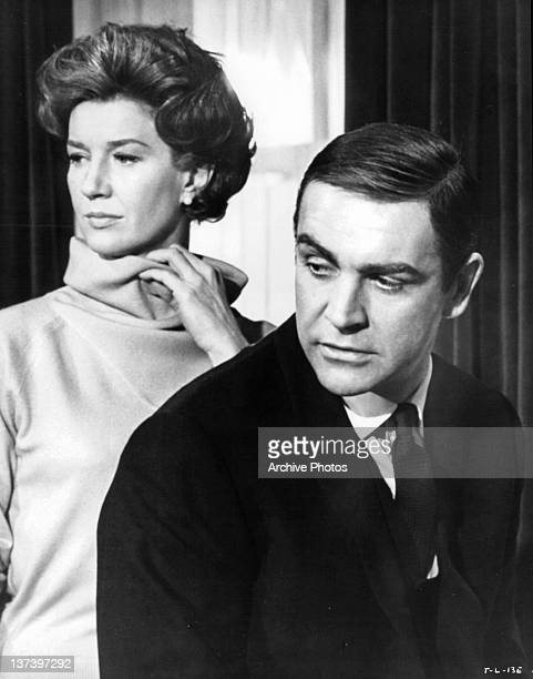 Lois Maxwell standing behind Sean Connery in a scene from the film 'Thunderball', 1965.