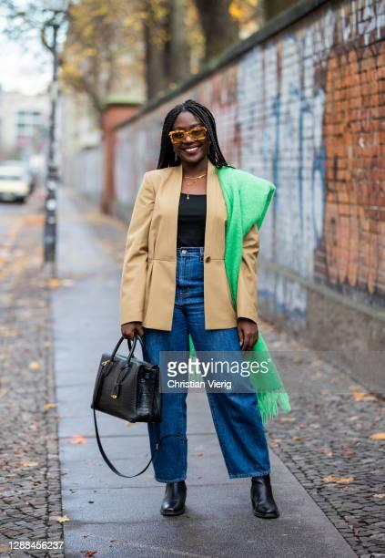 Lois Opoku is seen wearing beige blazer, green skirt, sunglasses Rodebjer, denim jeans Levis, Zara top in black MCM, necklace Ariane Ernst bag on...