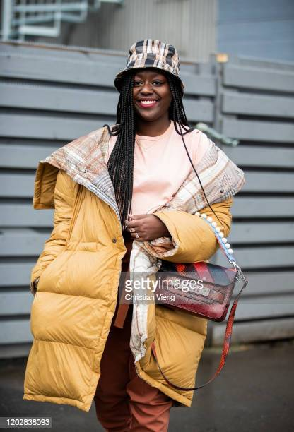 Lois Opoku is seen wearing bucket hat, Proenza Shouler bag, pink shirt, rust brown pants, beige coat outside Holzweiler during Copenhagen Fashion...