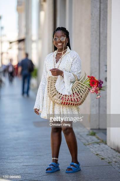 Lois Opoku is seen wearing dress MLM Label vintage Versace golden belt Chanel sandals straw bag Onvacay jewellery Onvacy Wald Berlin sunglasses...