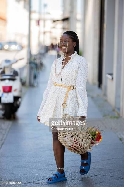 Lois Opoku is seen wearing dress MLM Label, vintage Versace golden belt, Chanel sandals, straw bag Onvacay, jewellery Onvacy & Wald Berlin,...