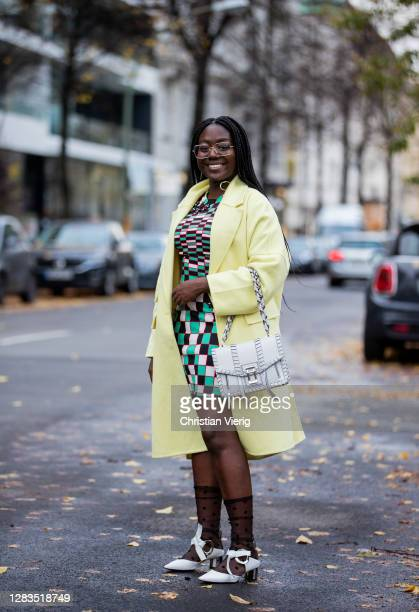 Lois Opoku is seen wearing green checkered dress Christopher Kane, Calzedonia sheer socks, white Proenza Schouler bag and heels, yellow coat Zara on...