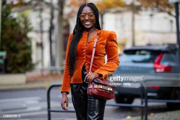 Lois Opoku is seen wearing orange velvet jacket Tory Burch, black pants Zara, Proenza Schouler bag, Ray Ban sunglasses on November 02, 2020 in...