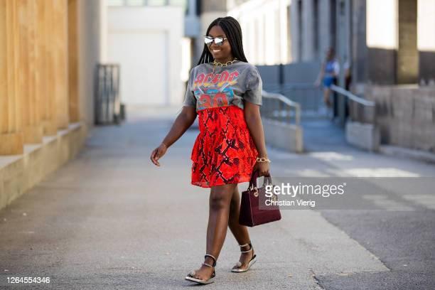 Lois Opoku is seen wearing red skirt Lala Berlin Dior bag Ariane Ernst necklace Pilgrim bracelet Pull and Bear tshirt sandals Isabel Marant white...
