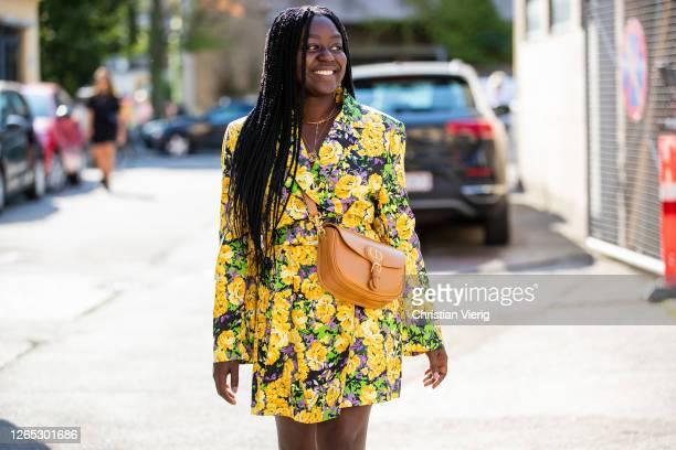 Lois Opoku is seen wearing yellow dress with floral print, brown Dior bag outside Samsøe & Samsøe during Copenhagen Fashion Week Spring/Summer 2021...