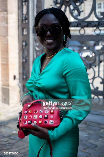 Lois Opoku outside MFPEN wearing green silk dress white sneakers and red bag with decorations during Copenhagen fashion week SS21 on August 12 2020...