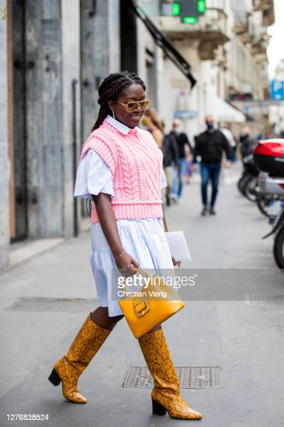 Lois Opoku seen wearing blue dress, pink knit, yellow bag, boots with snake print outside Bally during the Milan Women's Fashion Week on September...