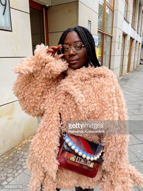 Lois Opoku wearing brown jacket from Roland Mouret, pants from nakd, shoes - Lacoste and proenza schouler bag strap from Fendi poses during an online...