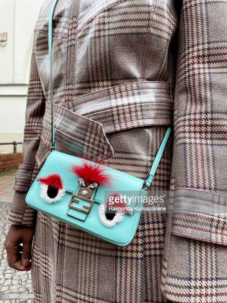 Lois Opoku wearing coat from Fendi, mini bag - Fendi, shoes - atp atelier and sunglasses from Burberry poses during an online street style photo...