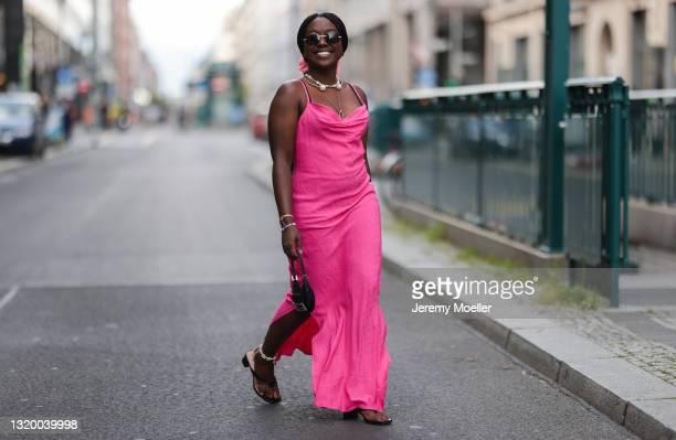 Lois Opoku wearing vintage Fendi mini bag, black Unisa heels, pink Mads Norgaard dress and Cartier shades on May 22, 2021 in Berlin, Germany.