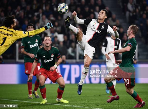 Lokomotiv Moscow's Russian goalkeeper Guilherme and Juventus' Portuguese forward Cristiano Ronaldo go for the ball before colliding during the UEFA...