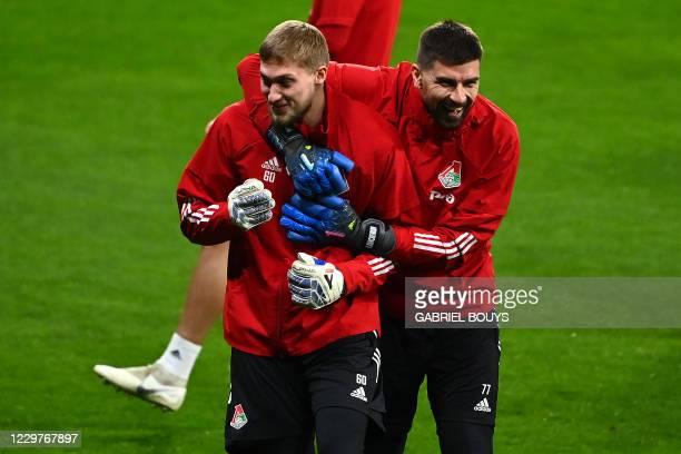 Lokomotiv Moscow's Russian goalkeepers Andrey Savin and Anton Kochenkov joke during a training session at the Wanda Metropolitano Stadium in Madrid...