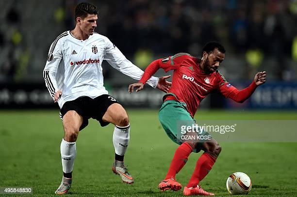 Lokomotiv's Portuguese midfielder Manuel Fernandes evades Besiktas' German forward Mario Gomez during the UEFA Europa League group H football match...