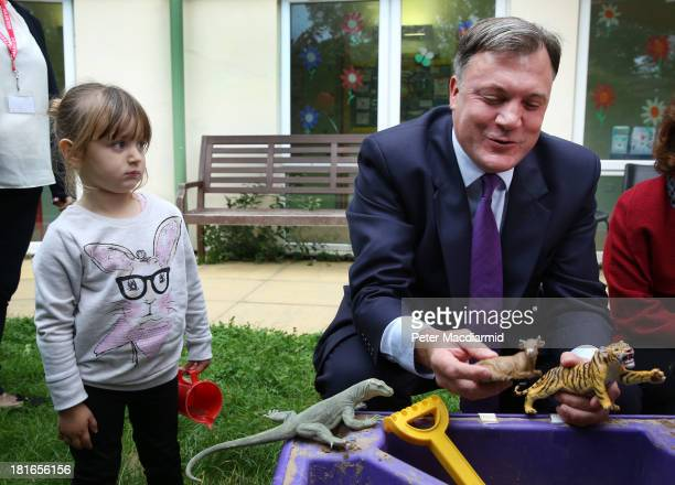 Lola aged two looks on Shadow Chancellor Ed Balls pulls a face as he plays at the sandpit at the Roundabout Children's Centre on September 23 2013 in...