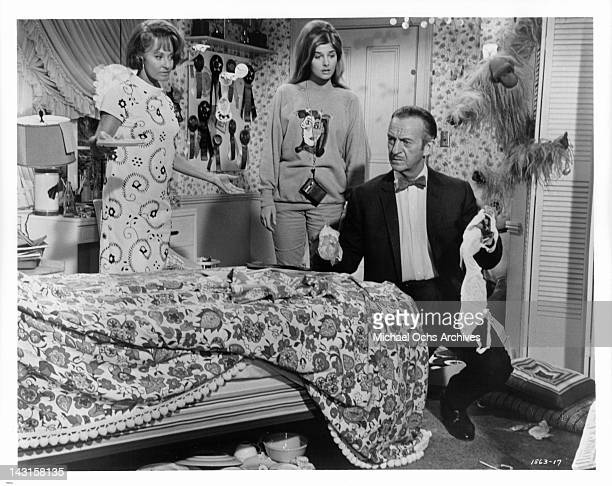 Lola Albright and Cristina Ferrare looks at David Niven holding a bra in a scene from the film 'Impossible Years' 1968