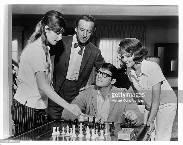 Lola Albright and David Niven watch as Cristina Ferrare makes a chess move in a scene from the film 'Impossible Years' 1968