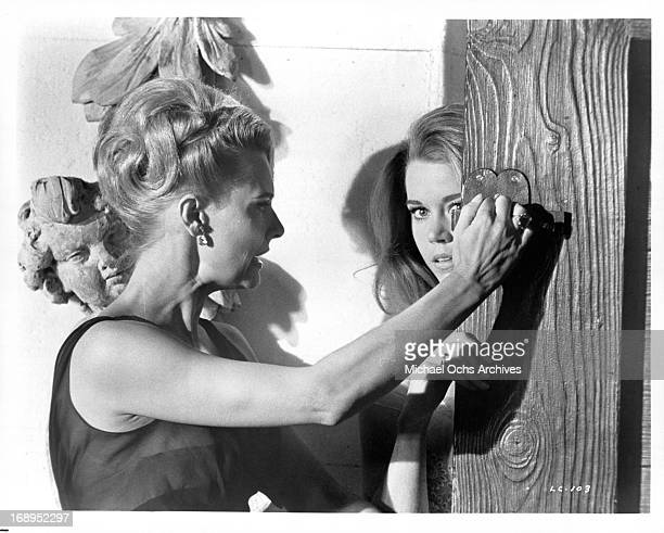 Lola Albright holds the door as Jane Fonda enters in a scene from the film 'Joy House' 1964