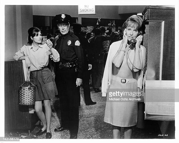 Lola Albright telephones for help as Cristina Ferrare is getting questioned by a police officer in a scene from the film 'Impossible Years' 1968