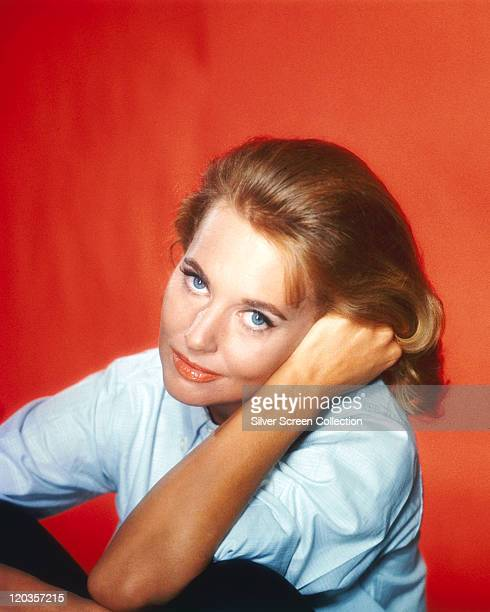 Lola Albright US actress wearing a light blue blouse with the sleeves rolled up in a studio portrait against a red background circa 1960