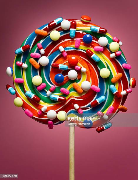 Lollipop coated with pills, close-up