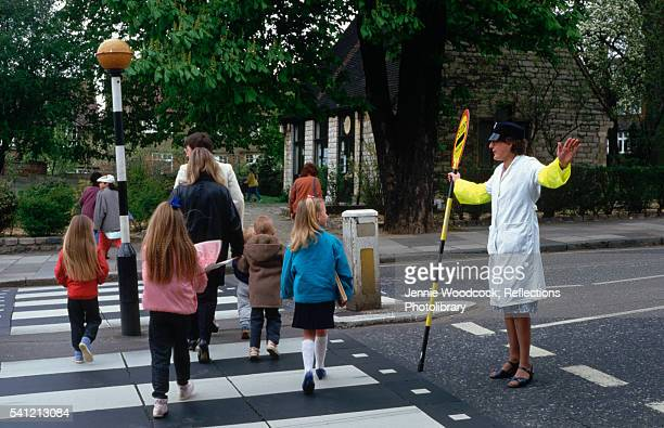Lollipop Lady Halting Traffic to Allow Children and Parents to Cross Road