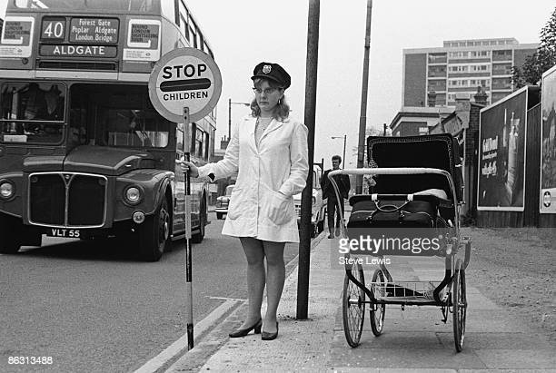 A lollipop lady holds a 'Stop Children' sign in the East End of London 1960s A number 40 bus to Aldgate passes by on the left