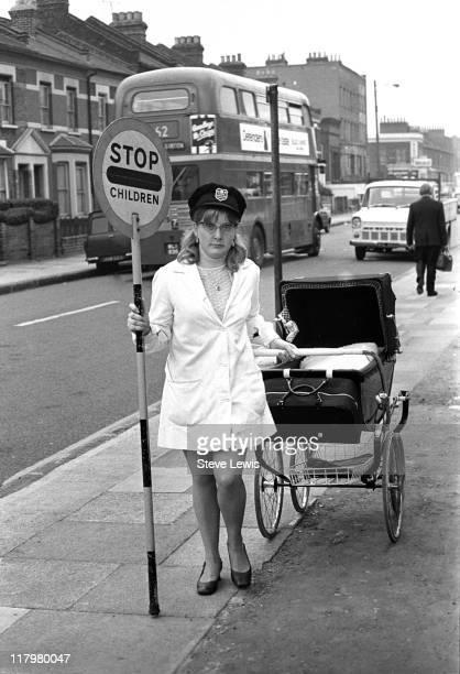A lollipop lady pulling a pram in London's East End circa 1970
