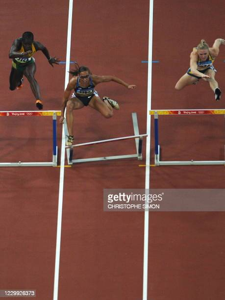 LoLo Jones of the US misses a hurdle as she competes against Jamaica's Deloreen Ennis-London and Australia's Sally McLellan during the women's 100m...