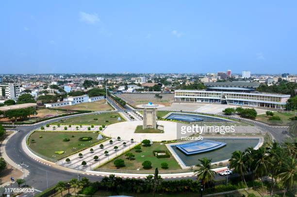 lomé, togo - independence square, the center of the country - palais de congrés on the top right and independence monument in the center of the square - togo stock pictures, royalty-free photos & images
