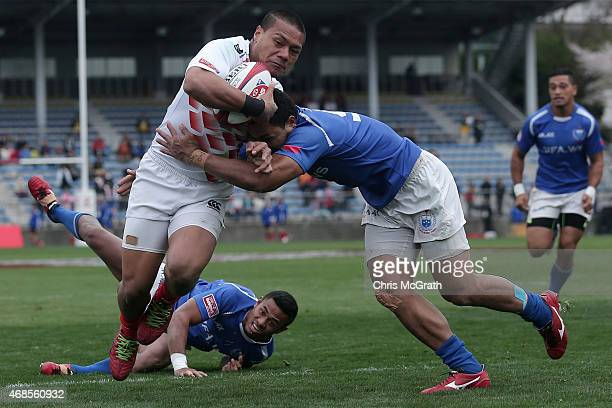 Lomano Lava Lemeki of Japan fends off Siaosi Asofolau of Samoa to score a try during the match between Japan and Samoa on day one of the Tokyo Sevens...