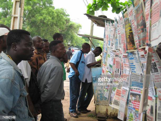 Men read the news of the helicopter crash that killed 22 people on board at a newspaper stand in Lome, 04 June 2007. A Russian co-pilot was the only...