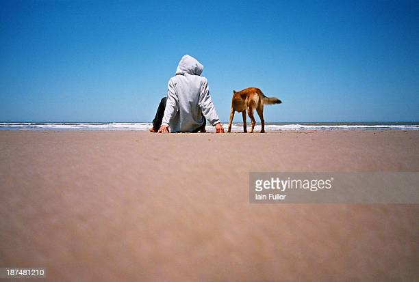 CONTENT] Lomo shot of a man in a hooded top sitting on a beach with his dog