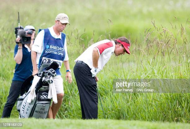 Phil Mickelson inspects his ball as the American's wayward drive found the heavy rough on the play-off 18th