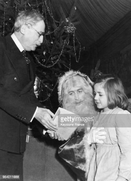 Léon Blum assisté du Père Noël distribue des jouets devant l'arbre de Noël à la présidence à Paris France en décembre 1946
