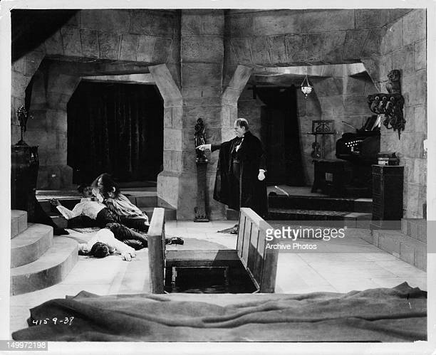 Lon Chaney gesturing to his victims in the catacombs in a scene from the film 'The Phantom Of The Opera' 1925