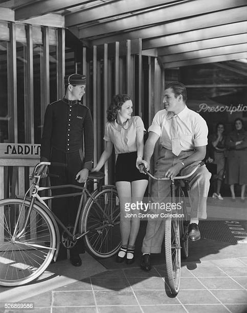 Lona Andre and Buster Crabbe leave their bicycles with the valet in front of Sardi's restaurant in Hollywood