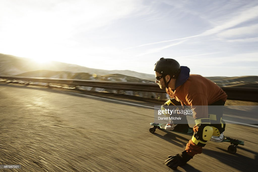 Lonboard skateboarder going down a road at sunset. : Stock Photo