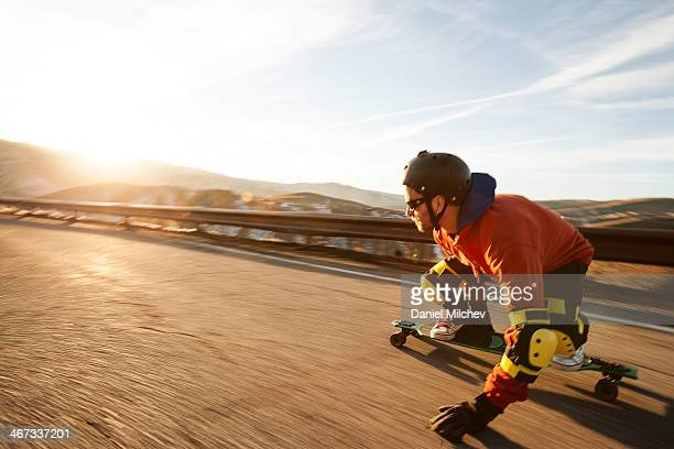 Lonboard skateboarder going down a road at sunset.
